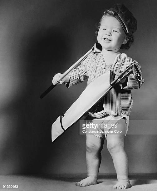 toddler playing with miniature golf clubs - constance bannister stock photos and pictures