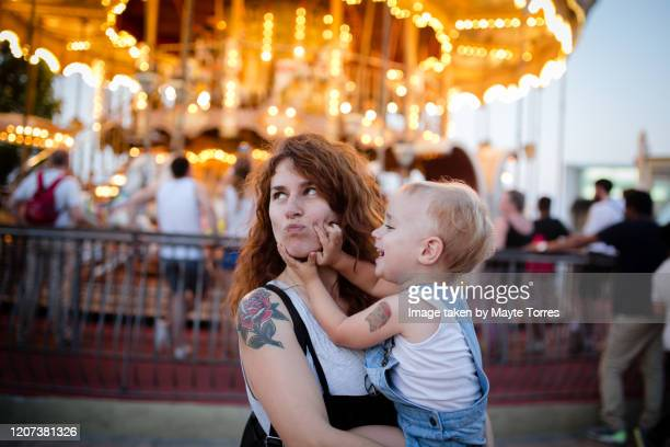 toddler playing with mom's face in front of carrousel - madre soltera fotografías e imágenes de stock