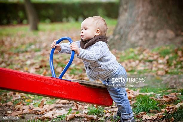Toddler playing with swing on playground, Osijek, Croatia