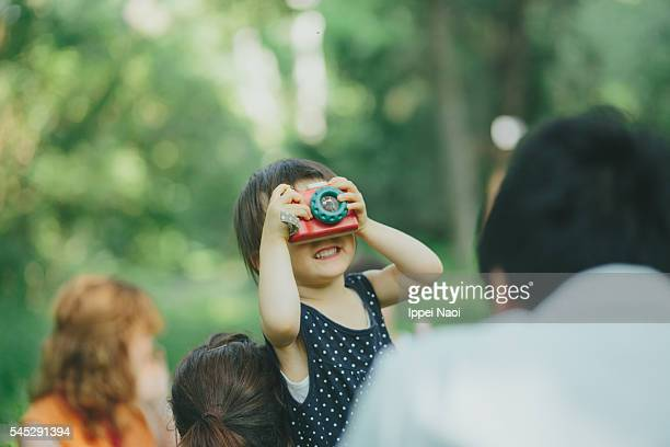 Toddler playing with wooden toy camera at park