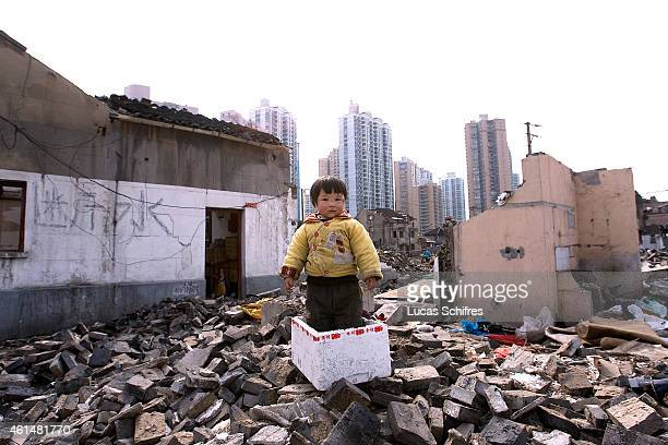 A toddler plays in rubble in an old neighborhood in the process of being demolished to make way to more modern residences like the ones in the...