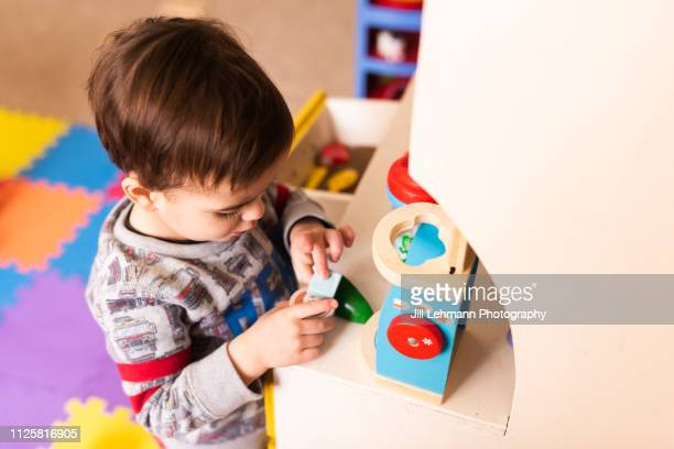 toddler plays with vintage kitchen on play mat with play food and utensils. shot above subject.  he is playing with a coffee maker. - jouer photos et images de collection