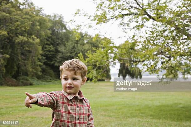 Toddler pointing to something of interest in park