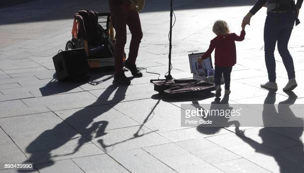 Toddler putting change into buskers guitar case