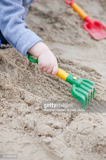 Toddler raking sand, cropped