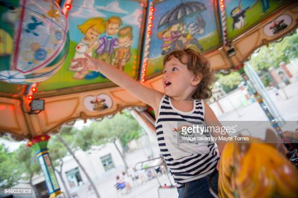 Toddler reaching for ball at the carrousel