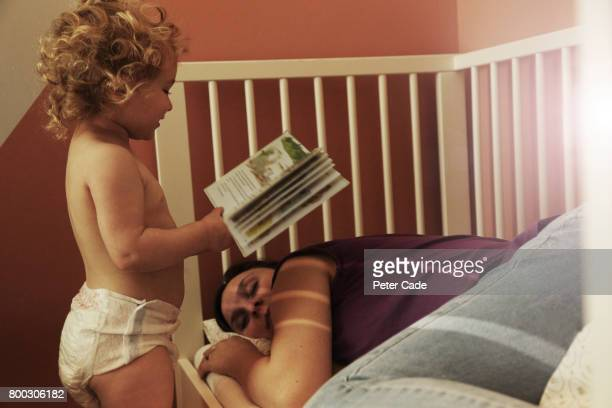 Toddler reading mother a book while she is asleep in a cot