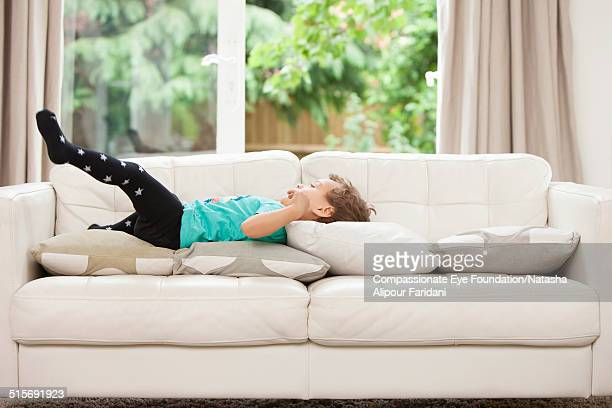 toddler relaxing on sofa - boys wearing tights stock photos and pictures