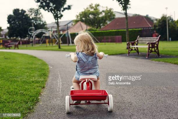 toddler riding a tricycle outdoors - sally anscombe stock pictures, royalty-free photos & images