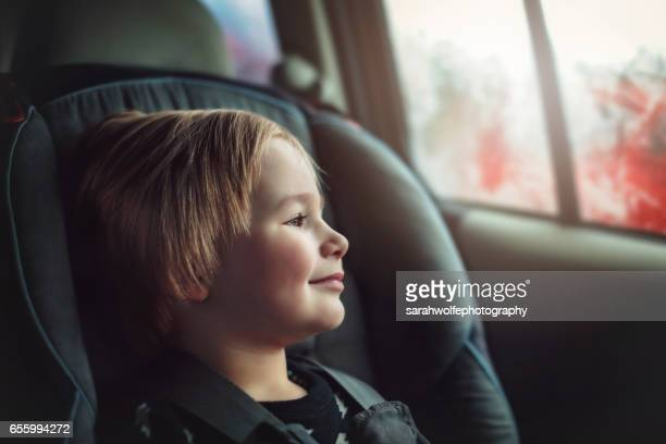 Toddler riding in his car seat during a road trip