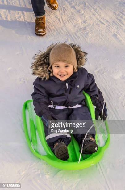 Toddler riding on green baby sled
