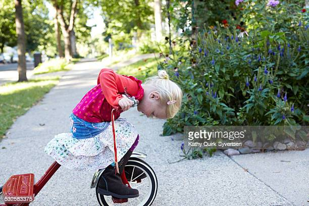 Toddler riding tricycle on the sidewalk