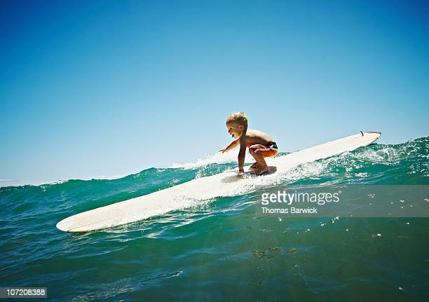 Toddler riding wave standing on surfboard