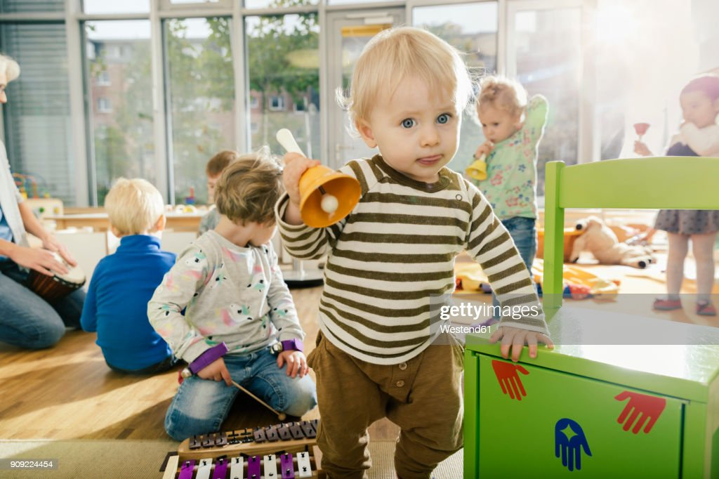 Toddler ringing a bell in music room of a kindergarten : Stock Photo