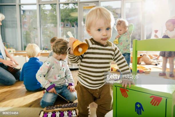 toddler ringing a bell in music room of a kindergarten - kindergarten stock-fotos und bilder