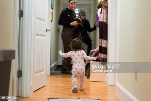 toddler running towards parents who've just returned home - ankunft stock-fotos und bilder