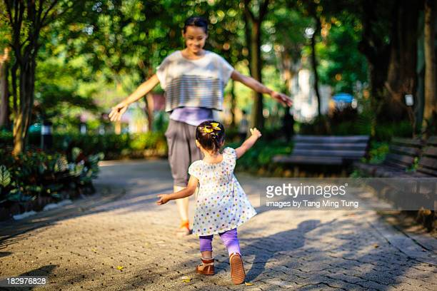 Toddler running towards young mom in a park