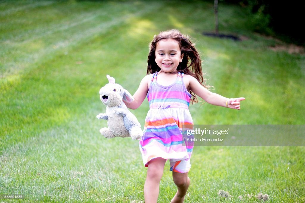 Toddler running with bunny doll : Foto stock