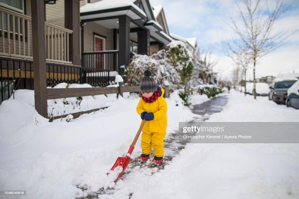 Toddler shoveling snow : Stock Photo