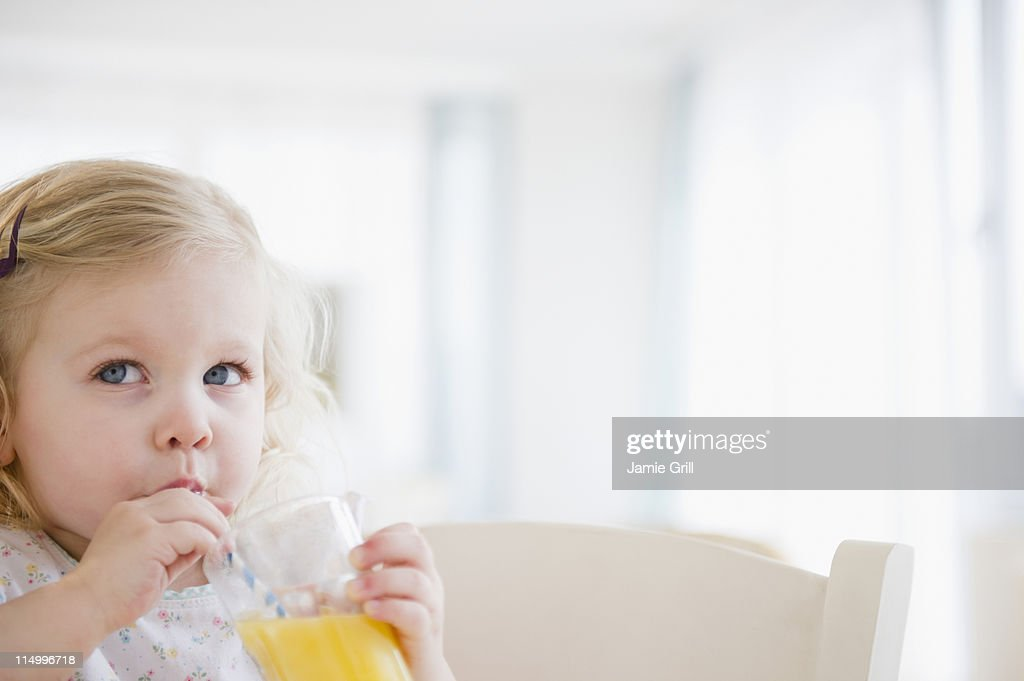 Toddler sipping orange juice through straw : Stock Photo