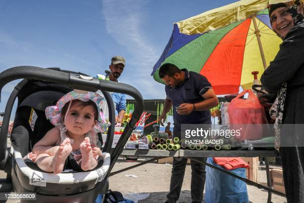 Toddler sitting in a child-walker looks on as people shop for produce at an open-air market in the Bedouin town of Rahat in Israel's southern Negev...