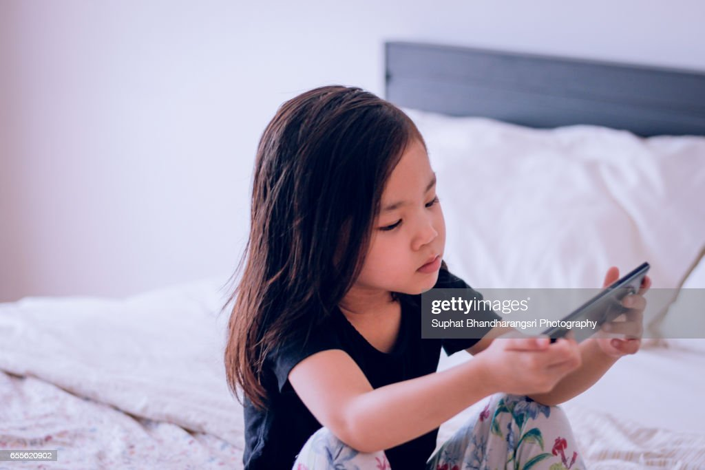Toddler sitting in bed watching video clip on smartphone : Stock Photo