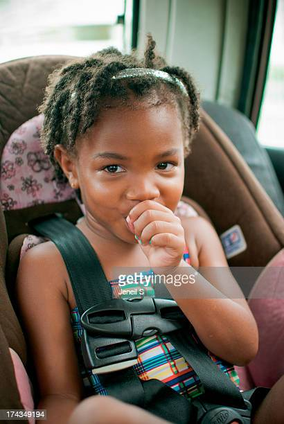 A toddler sitting in her car seat