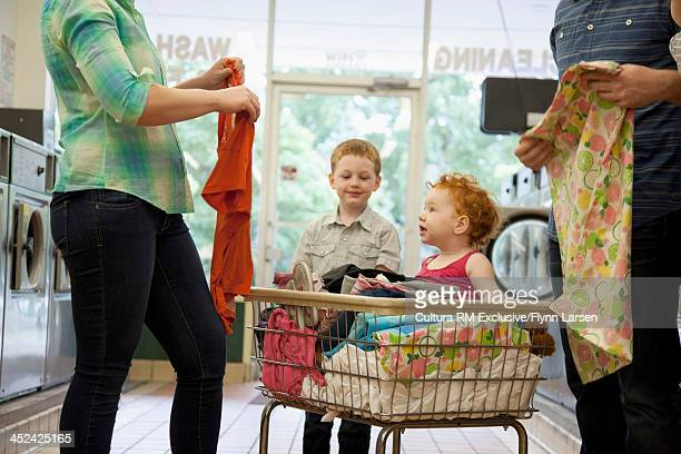 Toddler sitting in laundry basket, parents folding clothes