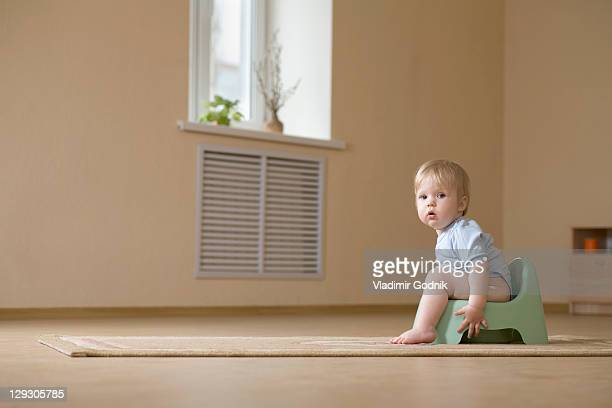 A toddler sitting on a potty chair, looking at camera