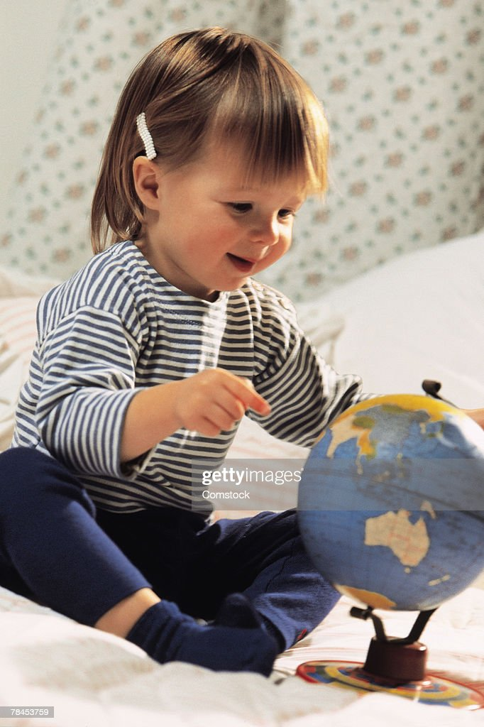 Toddler sitting on bed with a globe : Stockfoto