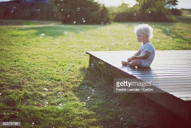 toddler sitting on deck, looking at soap bubbles - leander licht stock-fotos und bilder