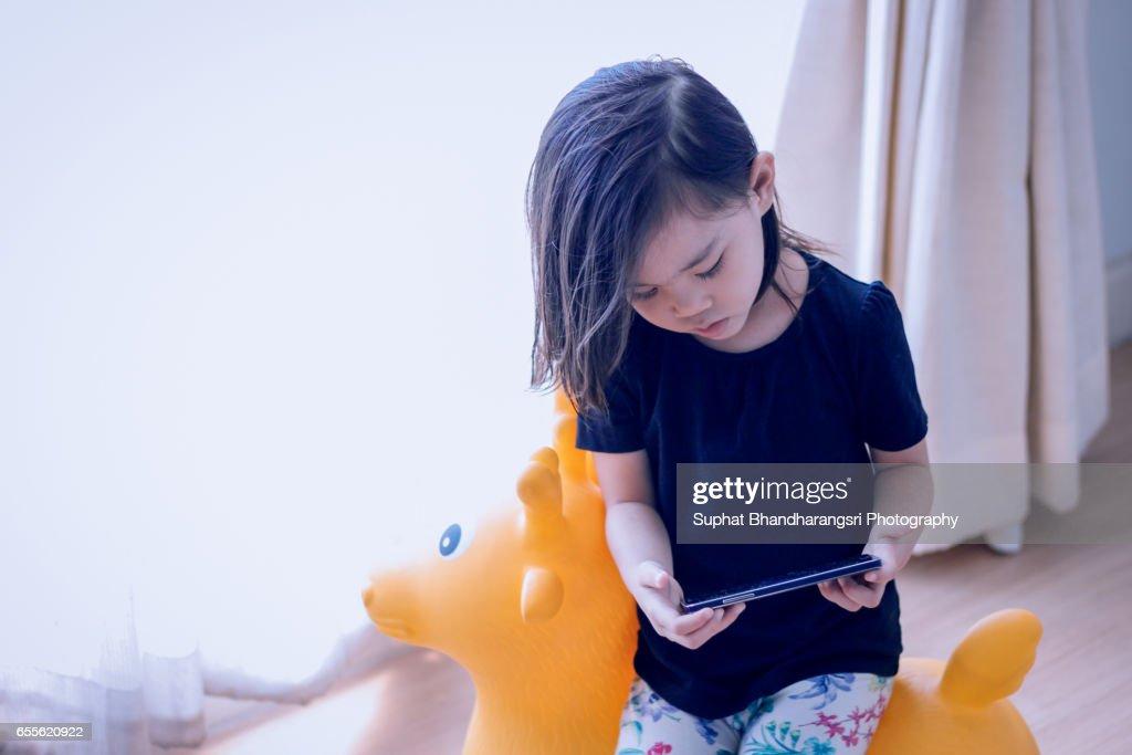 Toddler sitting on deer toy watching cartoon : Stock Photo