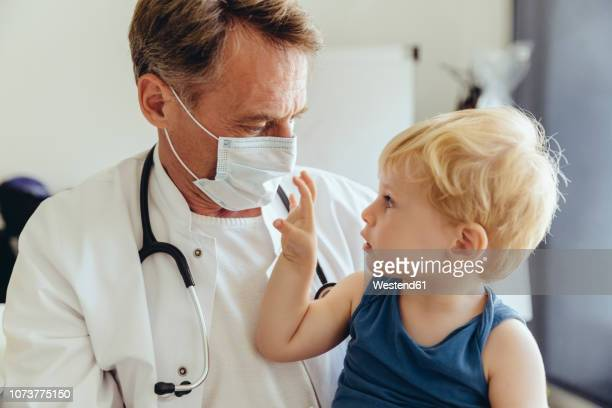 toddler sitting on lap of pediatrician, wearing protective mask - kinderarzt stock-fotos und bilder