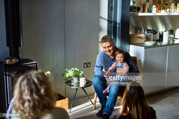 toddler sitting on mature man's lap - social distancing stock pictures, royalty-free photos & images