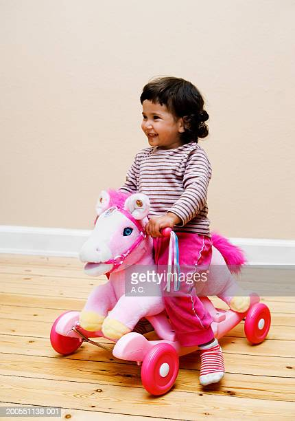 Toddler (21 months) sitting on pink rocking horse