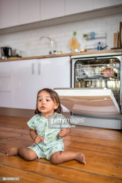 Toddler sitting on the floor in front of the dishwasher
