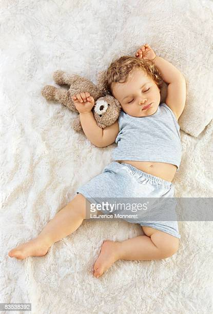 Toddler sleeping arms raised up with a Teddy bear