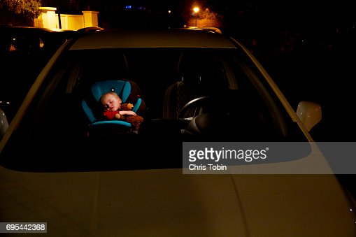 Toddler sleeping in car seat seen through front windshield