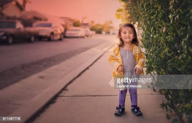 Toddler Smiles In Sidewalk Pose