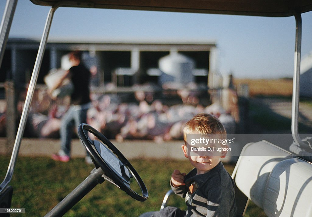 Toddler Smiling In Golf Cart On Farm : Stock Photo