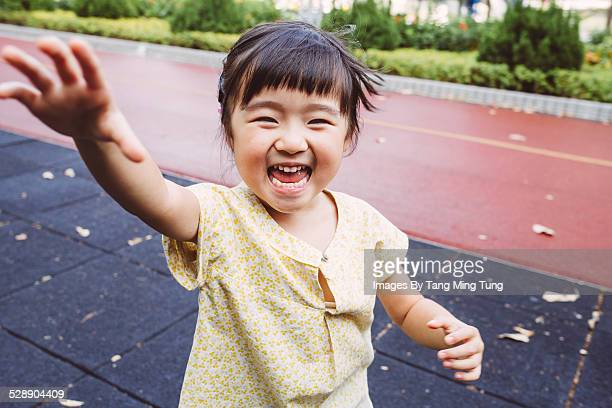 Toddler smiling joyfully at the camera in park