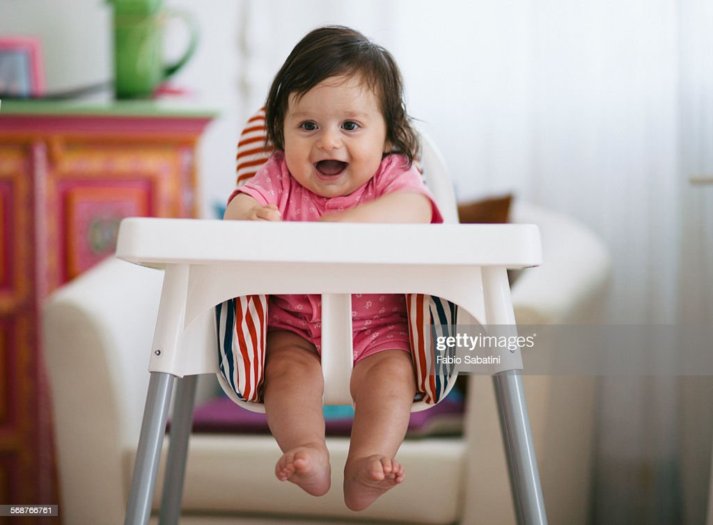 Toddler smiling on a high chair : Stock Photo