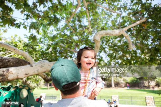 Toddler smiling with glee as father holds her up at tree filled park.