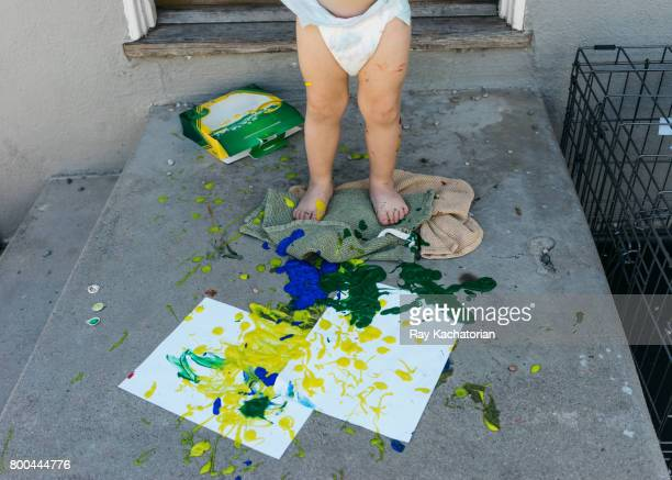 Toddler standing on art project