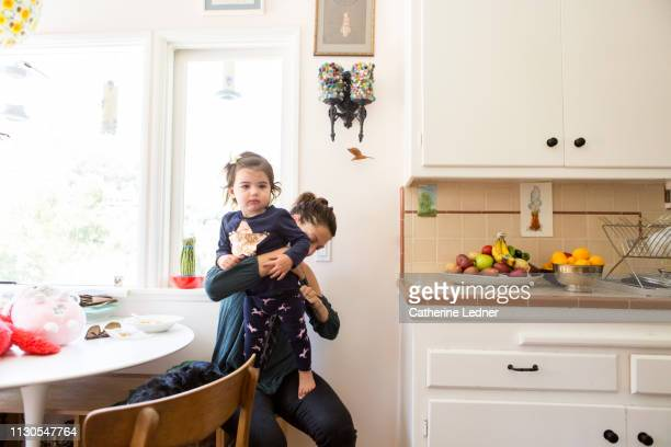toddler standing on mother's lap as she checks her diaper