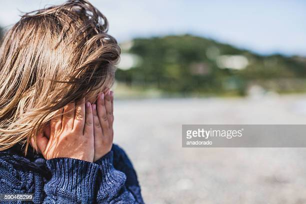Toddler standing on the beach covering her face with her hands