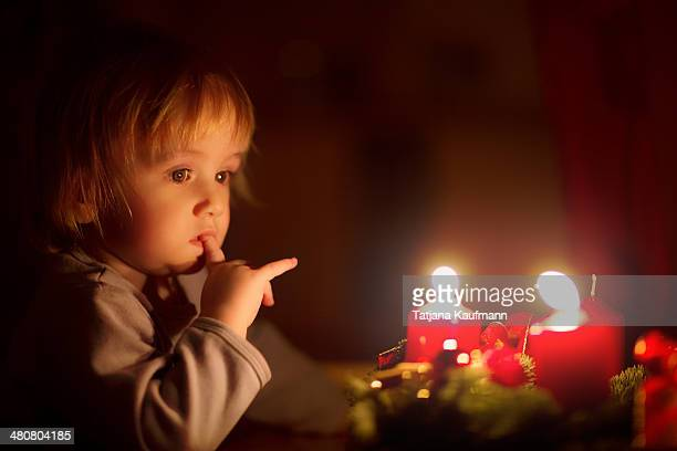 Toddler staring at two lit Advent Candles
