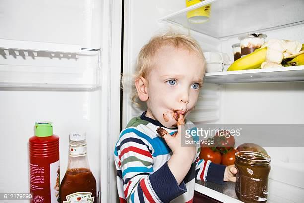 toddler sucking chocolate off finger - ondeugendheid stockfoto's en -beelden