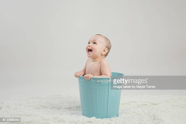 toddler taking a bath on a bucket