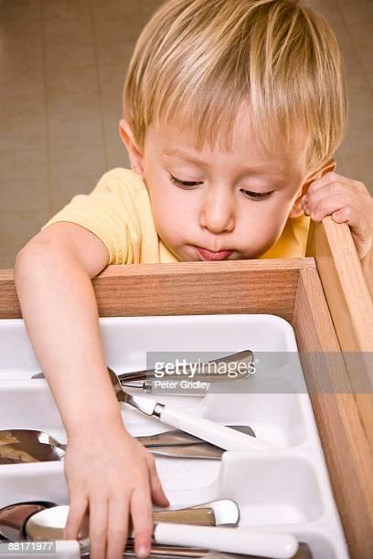 Toddler taking silverware out of drawer